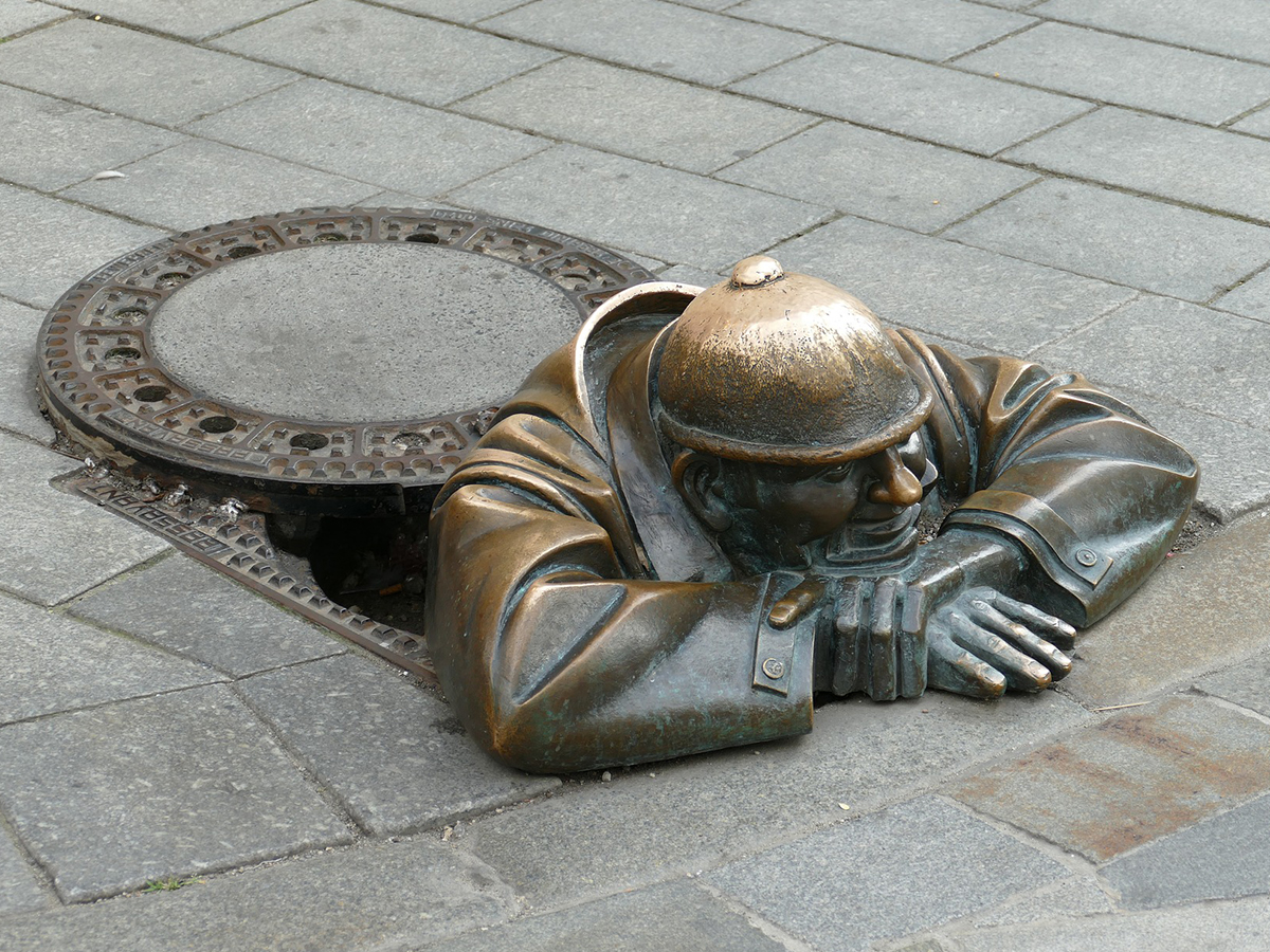 Statue of a man in a manhole resting his head on his arms on the pavement.